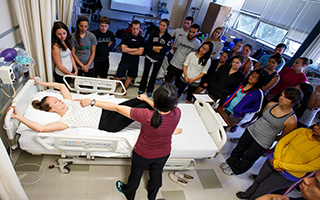 An instructor demonstrates for nursing students a patient procedure in the simulation lab.