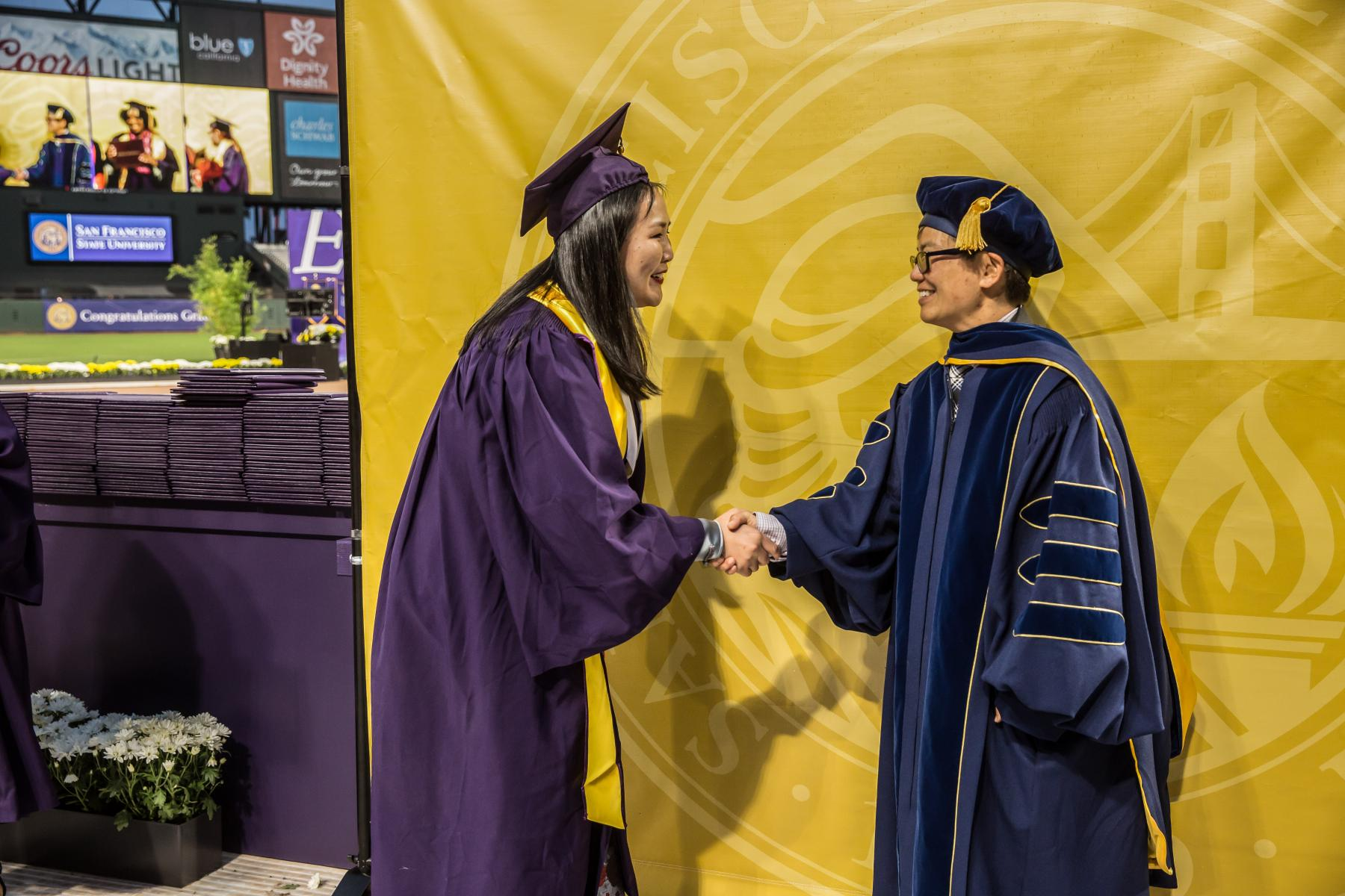 Dean Amy Sueyoshi greets a graduating student at Commencement