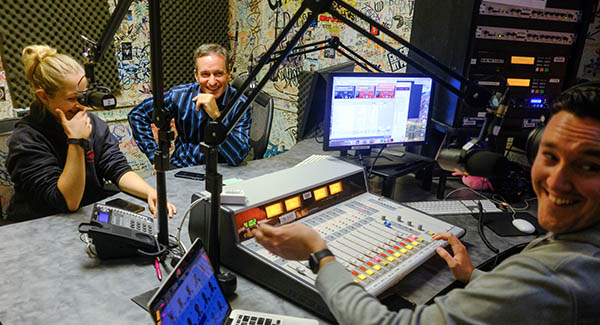 Student Emma Malki (left), Lecturer Dennis O'Donnell (center) and student Alexander Chase take a call in the KSFS studio.