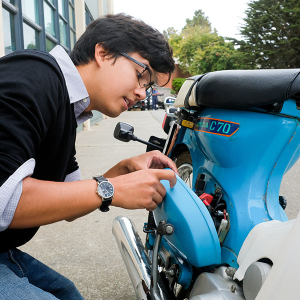 student fixing motorcycle