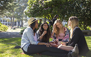 Business students enjoy the sun outside of the Business Building at SF State.