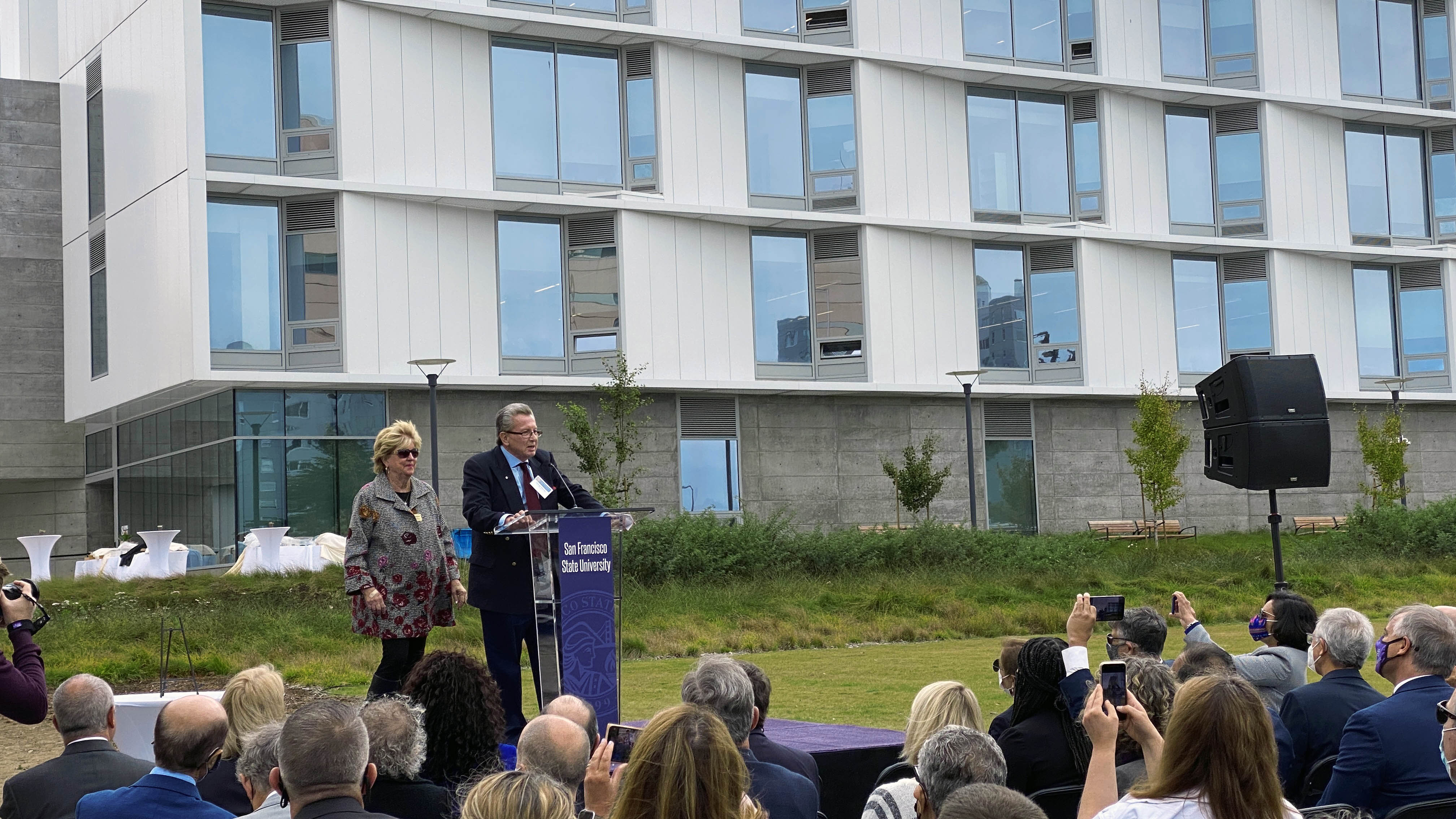 George and Judy Marcus give remarks while standing on a stage in front of Marcus Hall