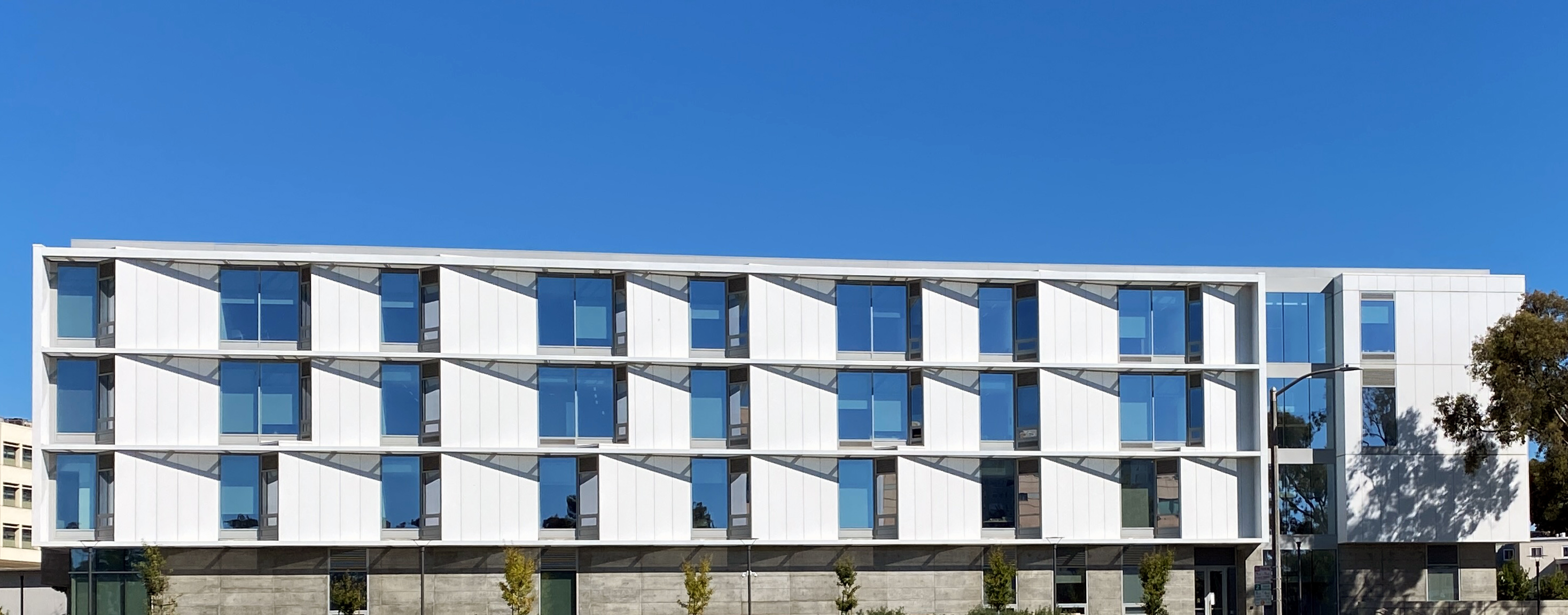 Marcus Hall exterior photo with bright blue sky mirrored in windows