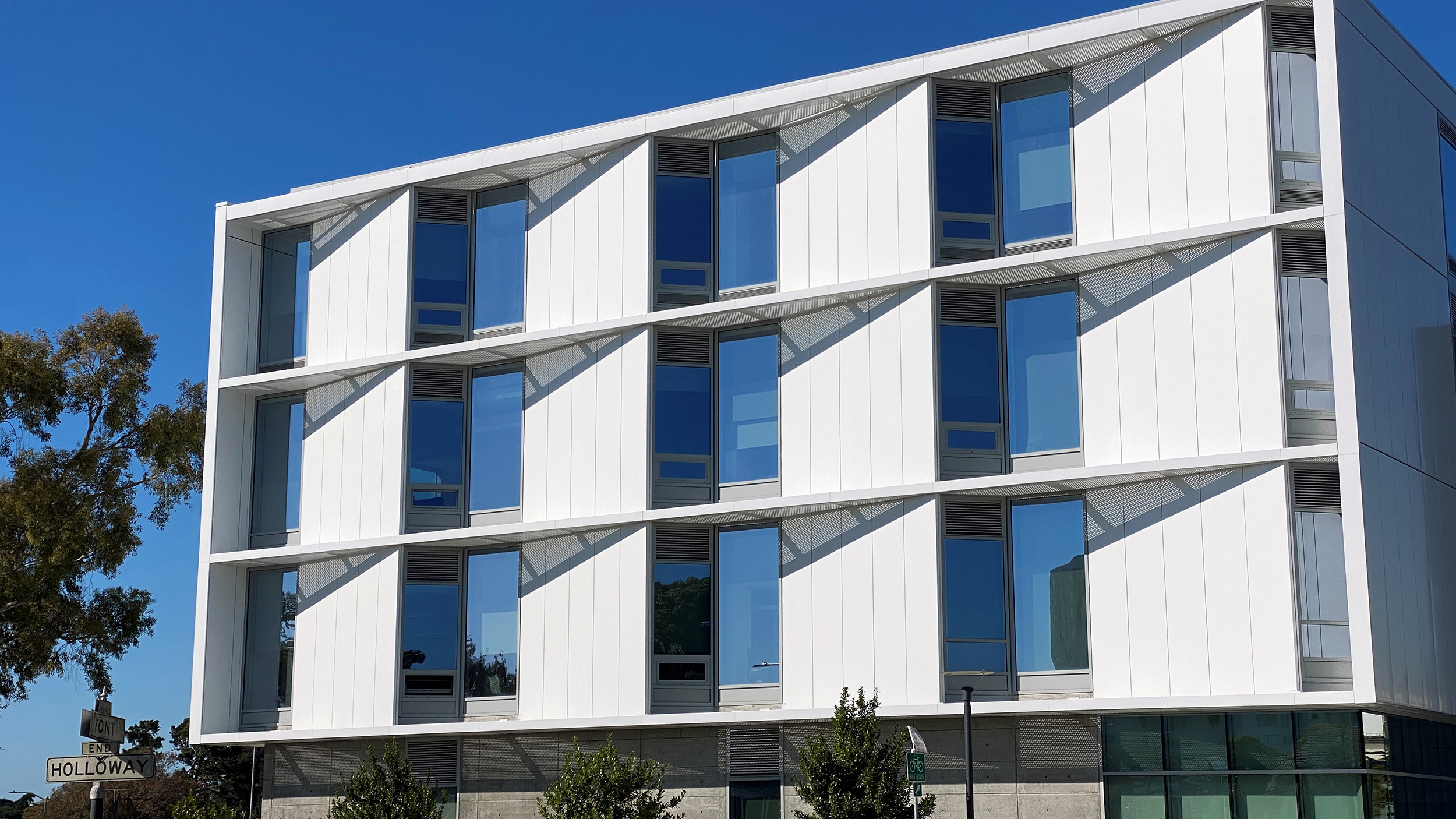 Marcus Hall exterior photo with bright blue sky mirrored in windows at San Francisco State University