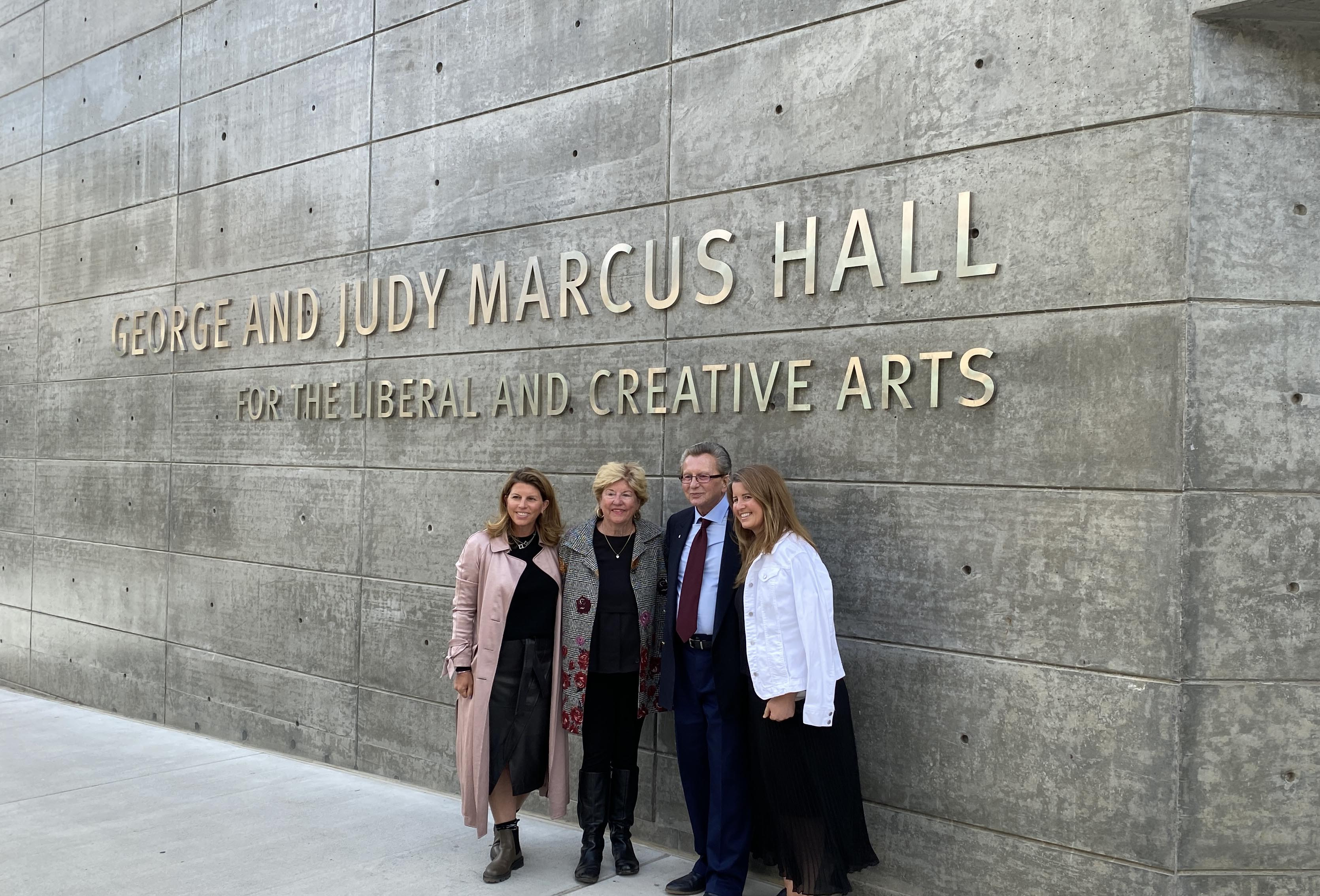 George & Judy Marcus stand in front of Marcus Hall, with the building's full name imprinted on the wall above their heads