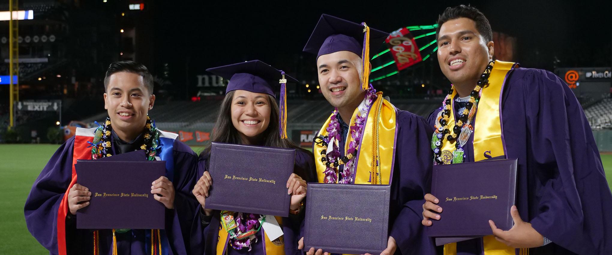 graduates at graduation holding their diplomas
